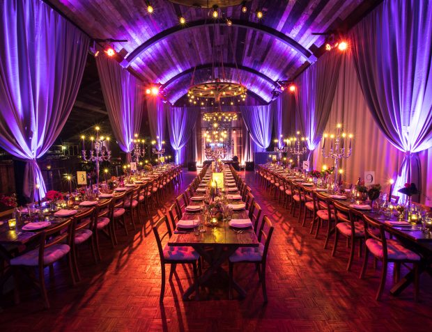 Barn interior table setting with drapes and lighting