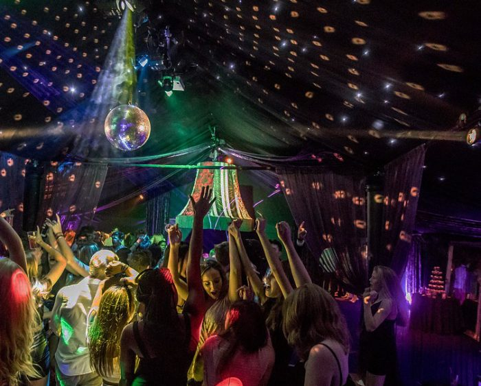 The Rage Pop-up Nightclub interior with mirror ball, top party music and dancers
