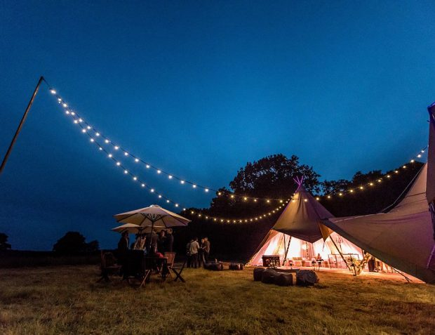 Giant hat tipis at dusk with lights