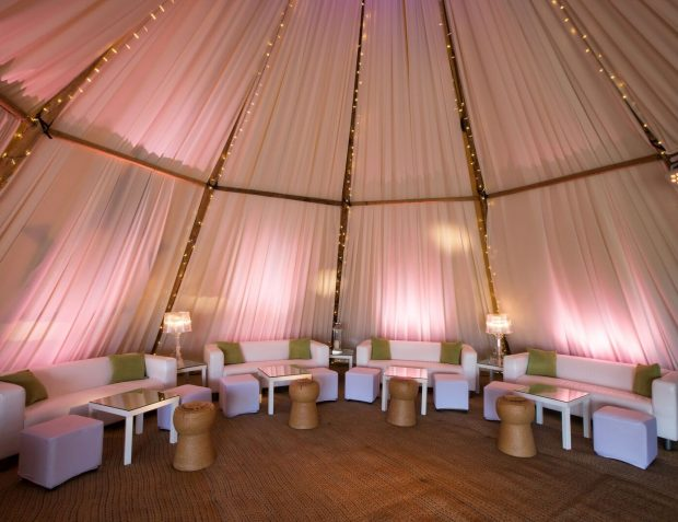Giant hat tipis interior with bespoke taught white pleated drapes between the timbers from the apex down to the floor.
