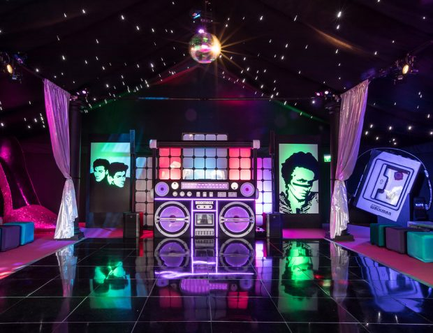 80's themed party nightclub marquee with bespoke boombox DJ booth, dance floor, star cloth ceiling and mirror ball, produced by Mirage Parties.