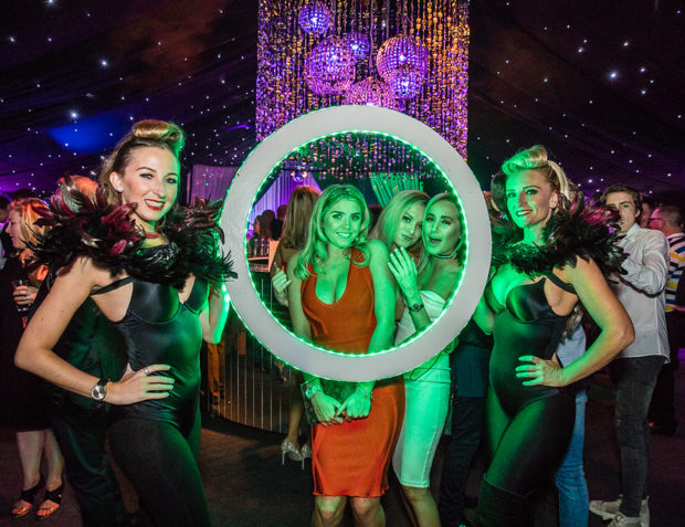 Party guests pose behind LED photo frame flanked by two pretty hostesses
