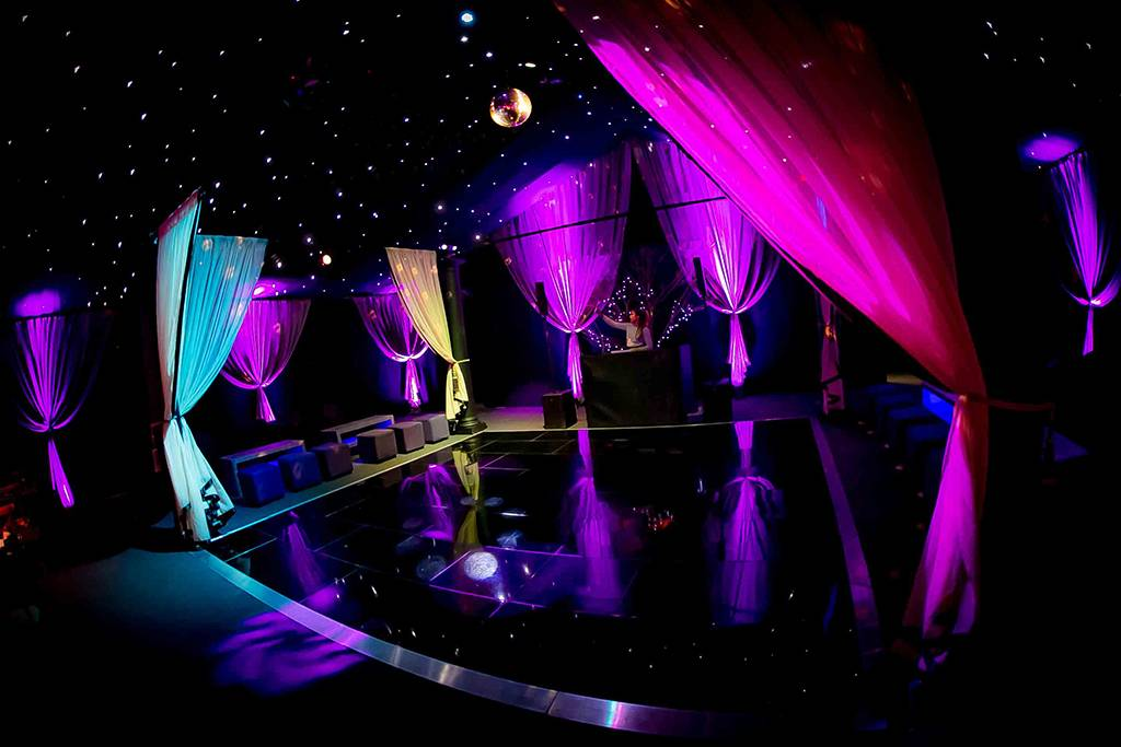Marquee dance floor with star cloth ceiling, mirror ball, draping and lights