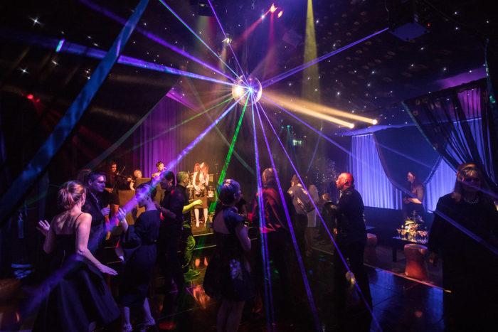 Lights reflect off mirror ball over guests on dance floor