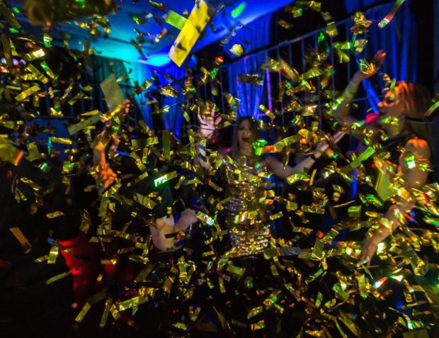 Private party guests dance under confetti cannon on the dance floor at an Ocean's 11 themed party
