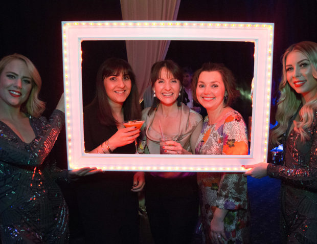 party guests have their photo taken in a LED photo frame