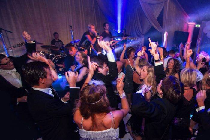Party guests on the dance floor rocking out to the best party bands