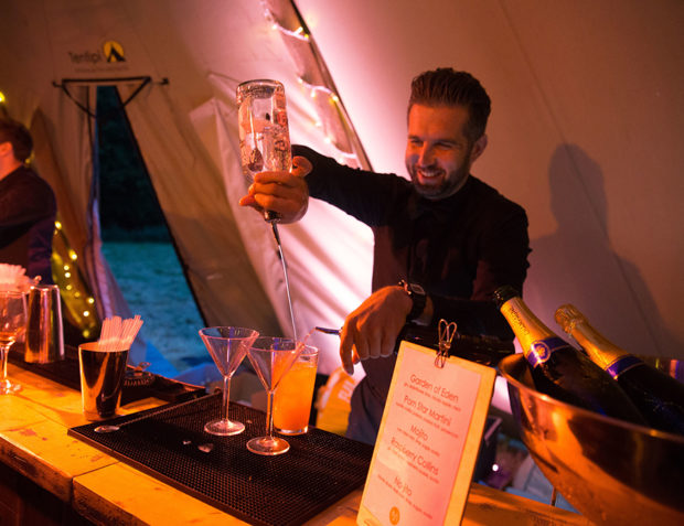 Bartender pours vodka behind a bar in a tipi