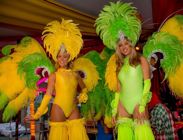 Two party hostesses on stilts inside party marquee