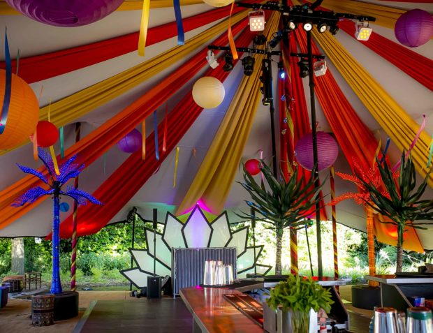 Interior styling carnival themed party marquee with draping, lighting, props, DJ booth and bar bar