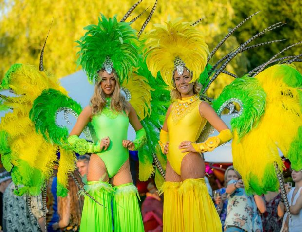 Two carnival stilt walkers in yellow and green