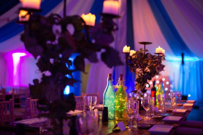 Fairy lights inside coloured glass bottles table setting