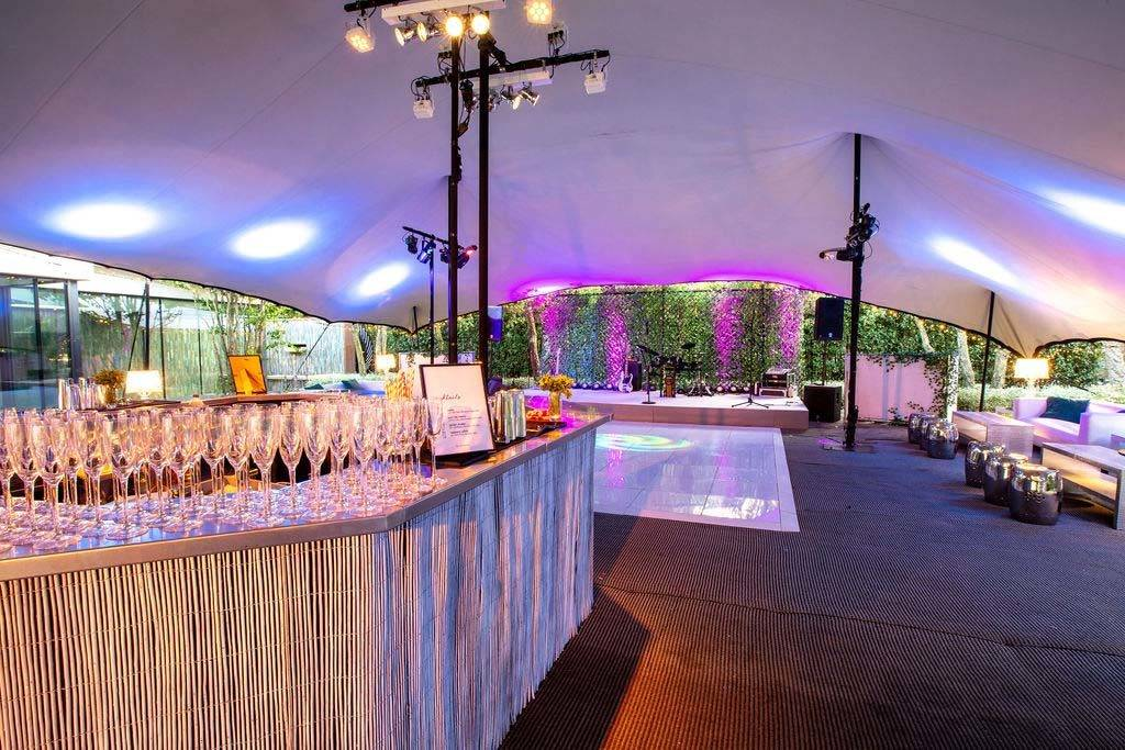White rattan bar and white dance floor in stretch tent in London
