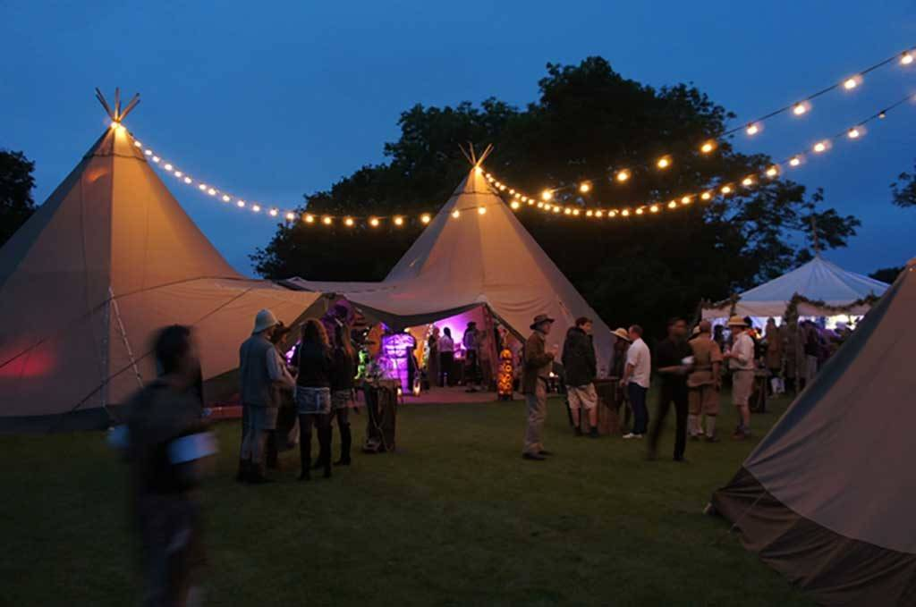 Party Tipi's at night with festoon lighting and party guests