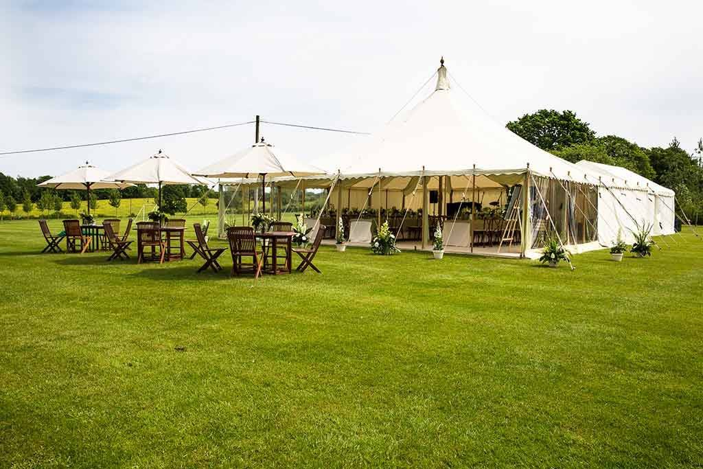 Traditional marquees at a garden party with outside tables
