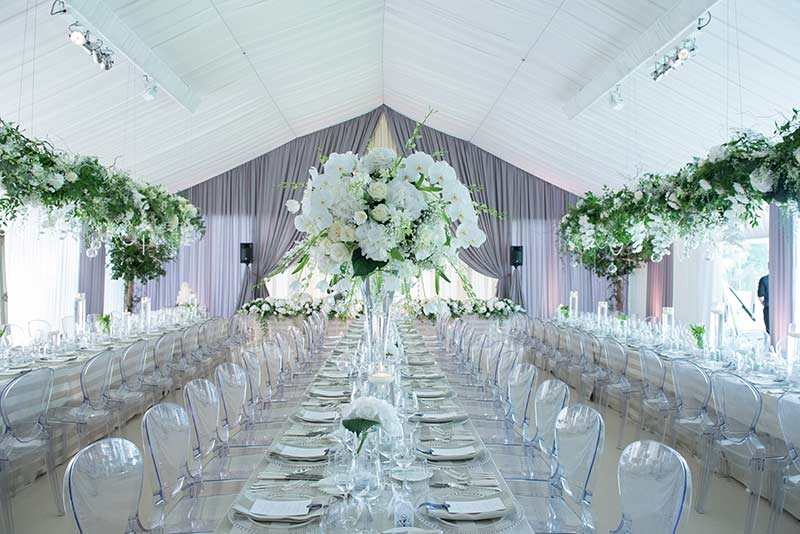 Wedding marquee setting with tall floral displays and hanging floral displays