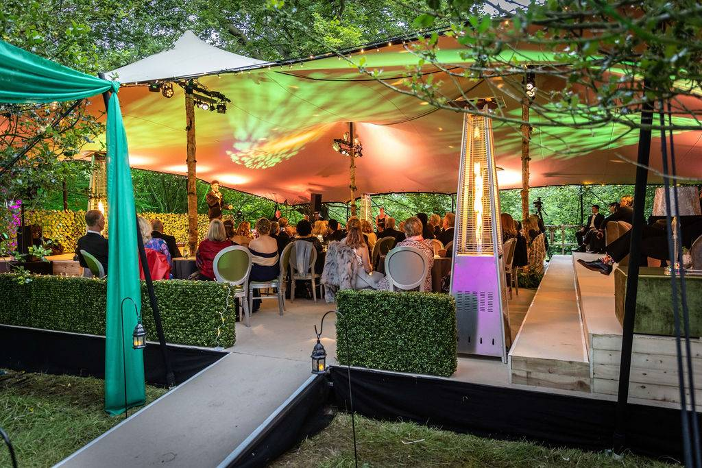 guests watching cabaret in a woodland setting